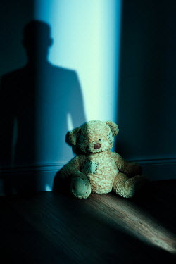 Magdalena Russocka Shadow of man and teddy bear in empty room at night