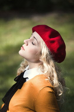 Magdalena Russocka Young woman in red beret sitting in grass