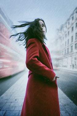 Natasza Fiedotjew Young woman in red coat in city on rainy day