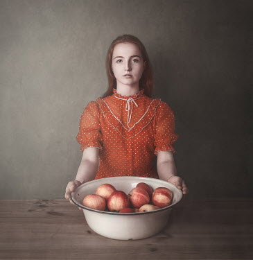 Anna Buczek Young woman in spotted red dress with bowl of apples
