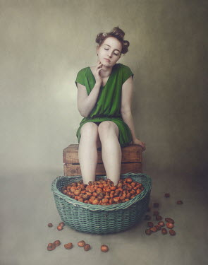 Anna Buczek Young woman in green dress with feet in basket of potatoes