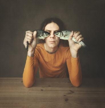 Anna Buczek Man at table holding fish over eyes