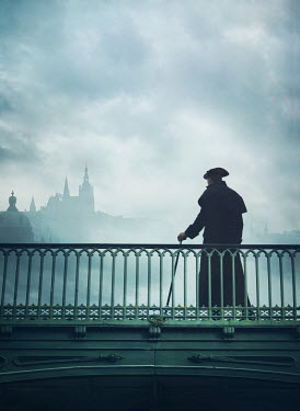 Mark Owen 0Man in coat and tricorne hat on bridge by cathedral