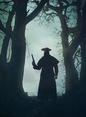 Mark Owen Man in coat and tricorne hat with pistol by bare trees