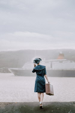 Natasza Fiedotjew Vintage lady with suitcase in port looking at cruise ship