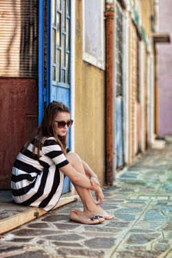 Beata Banach Young woman in striped dress sitting on doorstep