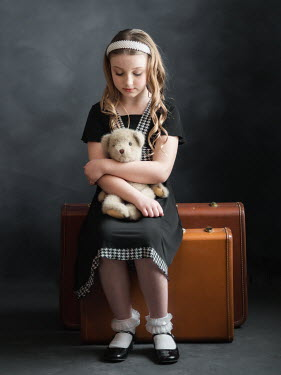 Elisabeth Ansley Girl in black vintage dress holding teddy bear sitting on suitcase