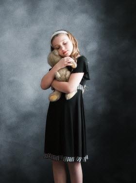 Elisabeth Ansley Girl in black vintage dress hugging teddy bear