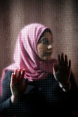 Mohamad Itani Young woman in pink headscarf behind window