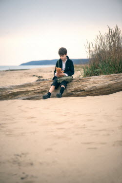 Galya Ivanova BOY HOLDING TEDDY SITTING ON BEACH Children
