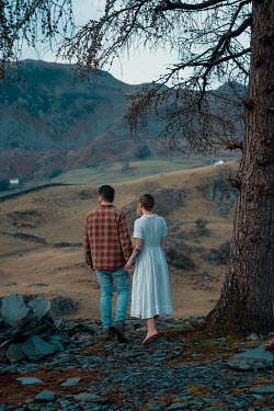 Rekha Garton COUPLE HOLDING HANDS IN COUNTRYSIDE AT DUSK Couples