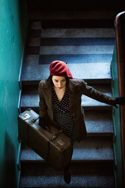 Svetoslava Madarova GIRL CARRYING SUITCASE ON STEPS IN BUILDING Women
