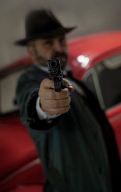 Jaroslaw Blaminsky MAN IN HAT POINTING GUN BY RED CAR Men