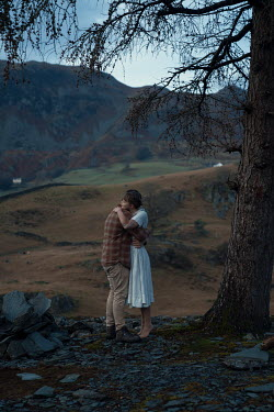 Rekha Garton COUPLE EMBRACING IN COUNTRYSIDE AT DUSK Couples