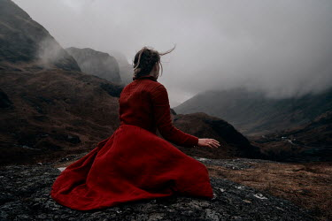 Rekha Garton WOMAN SITTING IN MISTY WINDY LANDSCAPE Women