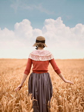 Mary Wethey HISTORICAL WOMAN IN WHEAT FIELD FROM BEHIND Women