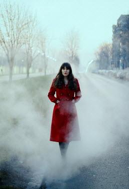 Felicia Simion Woman in red coat walking on foggy street