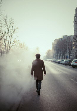 Felicia Simion Man with brown coat walking on foggy street