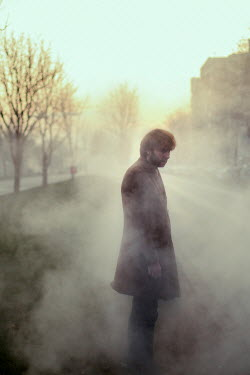 Felicia Simion Man with brown coat standing on foggy street