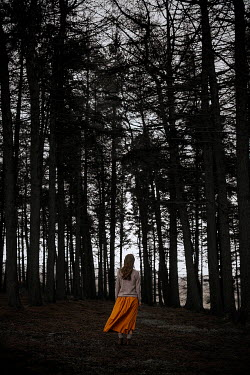 Shelley Richmond Young woman in sweater and orange skirt near trees