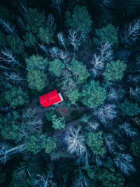Magdalena Russocka aerial view of man's body lying by house in forest