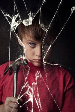 Kelly Sillaste Boy with hammer behind broken glass