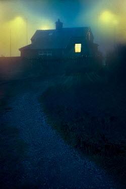 Lee Avison house at night in fog with window light