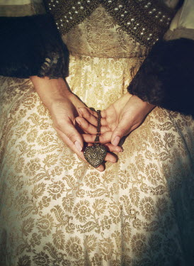 Mark Owen Hands of medieval woman holding heart locket