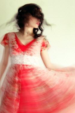 ILINA SIMEONOVA Long exposure of woman in red dress dancing