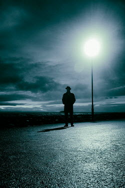 Tim Robinson Silhouette of man in hat and coat under street light