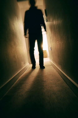 Tim Robinson Silhouette of man walking in corridor
