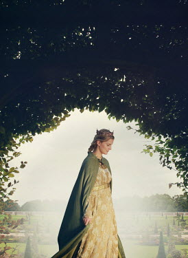 Mark Owen Young woman in medieval gown and cloak standing in garden
