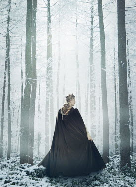 Mark Owen Young woman in medieval cloak walking through forest during winter
