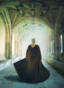Mark Owen Young woman in medieval cloak walking through cloister