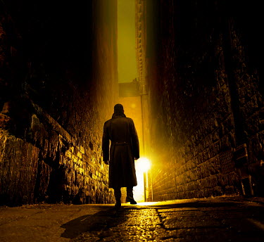 Stephen Mulcahey A silhouette of a man walking down a narrow alleyway