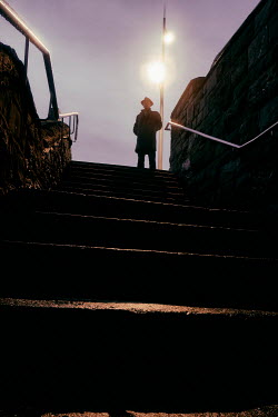 Tim Robinson SILHOUETTED MAN ON STEPS FROM BELOW Men