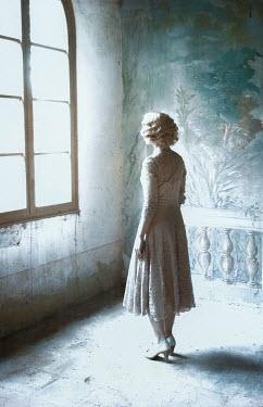 Nikaa BLONDE WOMAN WATCHING WINDOW INDOORS Women