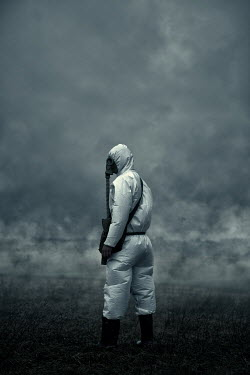 Magdalena Russocka man wearing antichemical suit and gas mask standing in smoky field