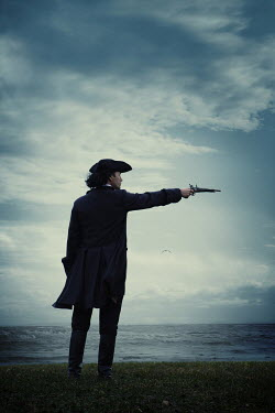 Magdalena Russocka historical man in tricorn hat and long jacket with flintlock standing by sea