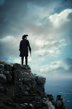 Magdalena Russocka historical man in tricorn hat and long jacket with flintlock standing on cliff by sea