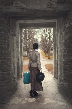Anna Buczek GIRL CARRYING SUITCASE AND HAT IN OLD BUILDING Women