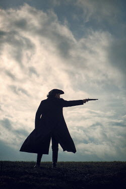 Magdalena Russocka historical man in tricorn hat and long coat with flintlock standing on hill