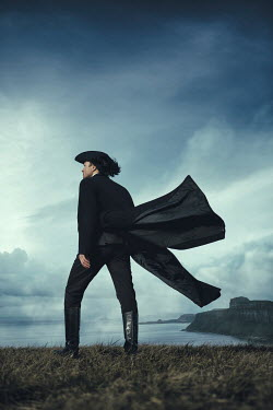 Magdalena Russocka historical man in tricorn hat and long coat standing on hill by sea
