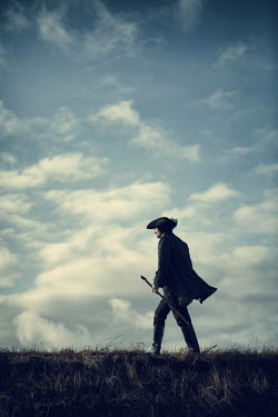 Magdalena Russocka historical man in tricorn hat and long jacket with cane walking on hill