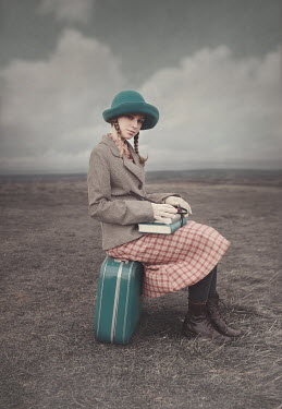 Anna Buczek GIRL WITH BOOK SITTING ON SUITCASE IN COUNTRYSIDE Women