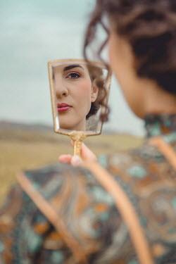 Joanna Czogala WOMAN WATCHING REFLECTION IN MIRROR IN COUNTRYSIDE Women