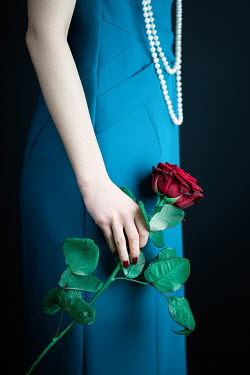Magdalena Russocka close up of elegant woman with pearl necklace holding red rose