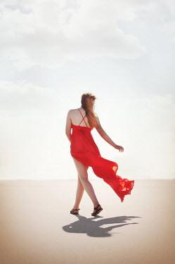 Buffy Cooper WOMAN IN RED SILK DRESS WALKING ON SAND Women