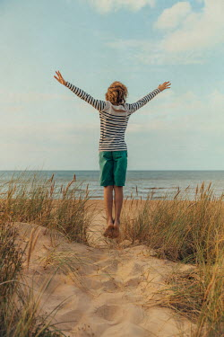 Katya Evdokimova BAREFOOT BOY JUMPING ON SANDY BEACH Children