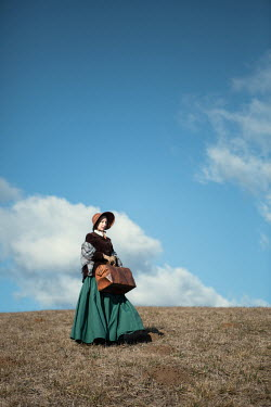 Magdalena Russocka historical woman with travel bag in countryside